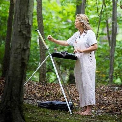 Patricia Griffin painting in the woods